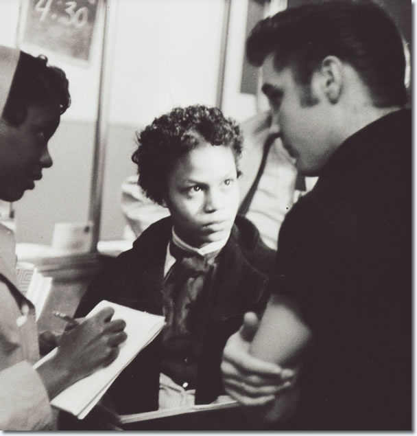 Elvis Presley talks as two young reporters listen attentively backstage at the Fox Theatre.