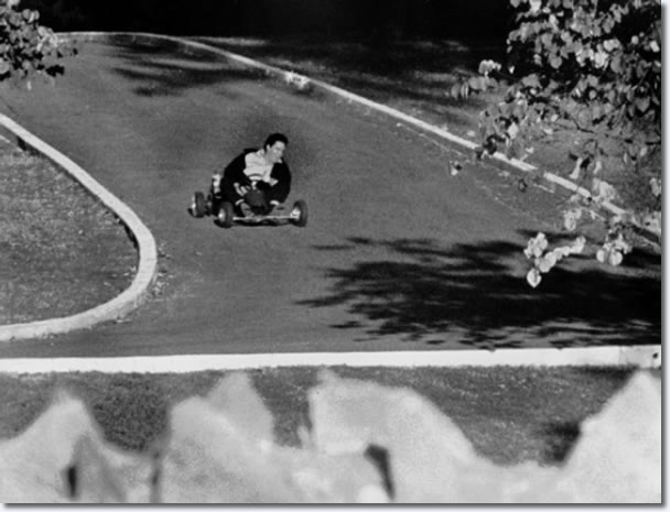 Elvis Presley on a go cart racing up the driveway of Graceland October 12, 1965.