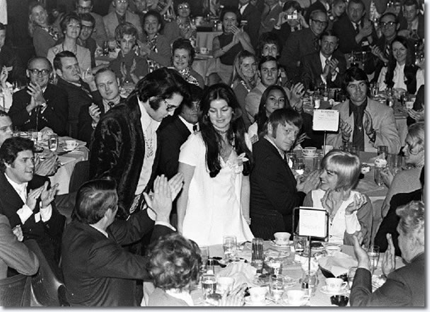 Elvis is being introduced with Priscilla beside him at the US Jaycee prayer breakfast.