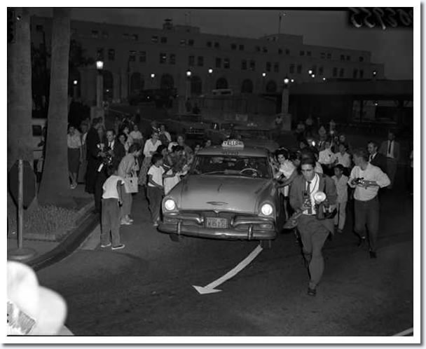 April 20, 1960 : Los Angeles Airport California : Elvis Presley proved he has the same old magic yesterday as screaming teenagers surrounded his taxi as it left Union Station. The faithful had waited four hours for their hero.