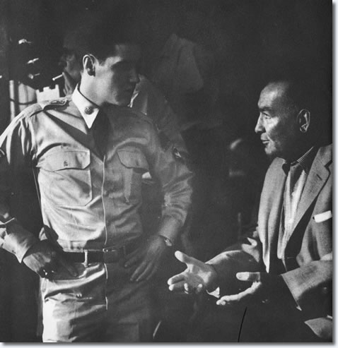 A rare behind the scenes shot of Elvis talking to Producer Hal Wallis.