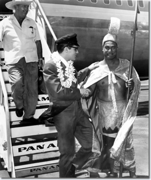 """Elvis Presley greeted by an island local as he arrives for filming of the 1962 movie, """"Girls!, Girls!, Girls!"""" Presley's manager, Col. Tom Parker, comes down the ramp behind him."""