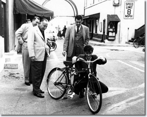 Hal Wallis and Hal Kanter present Elvis with his new 'Hound Dog' bike for use around the Paramount Studio complex