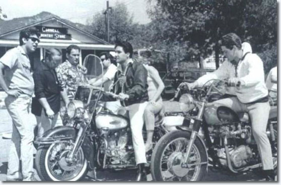 During shooting of Elvis movie 'Spinout' 1966 – left to right: Larry Geller, Marty Lacker, Alan Fortas, Joe Esposito, Elvis Presley, Deborah Walley on the bike behind Elvis, Jerry Schilling.