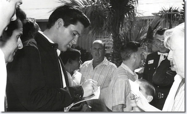 Elvis Presley signs autographs on the set of Viva Las Vegas. Colonel Parker watches everything.