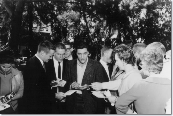 Elvis signs autographs whilst filming on location for the picture 'Wild In The Country'.